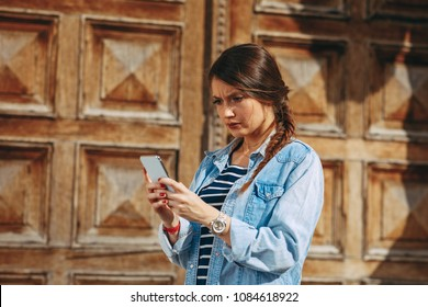 Young woman reads a bad message on the phone