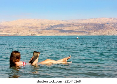 young woman reads a book floating in the waters of the Dead Sea in Israel
