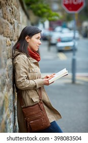 Young woman reads book on the street, urban shoot