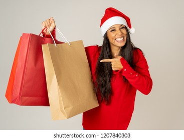 Young woman ready for christmas with paper shopping bags in red and Santa claus hat isolated grey background in being ready for christmas shopping gifts celebration consumerism and sales concept.