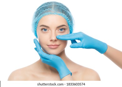 Young woman ready for rhinoplasty, doctor in blue gloves touching her nose, isolated on white background