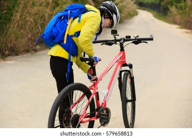 young woman ready to riding mountain bike on forest trail
