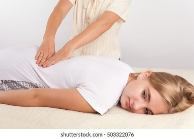 Young woman receives bowen therapy - massage for her back