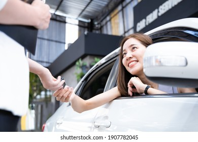 Young woman receives a key from car showroom after making car purchase contract.