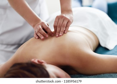Young woman receiving a back massage by professional therapist. Female patient is receiving treatment in a spa center.