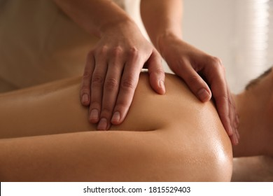 Young woman receiving back massage in spa salon, closeup