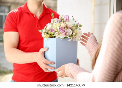 Young woman receiving beautiful flowers from delivery man at home