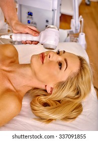 Young woman receiving electric facial microdermabrasion massage at beauty salon.
