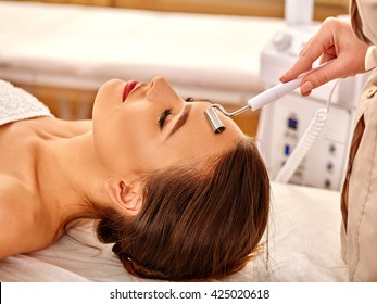 Young woman receiving electric galvanic face spa massage at beauty salon. Used for  therapy of multifunctional electroporation  device.