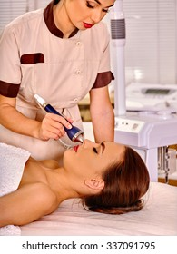 Young woman receiving electric ultrasonic facial massage at beauty salon.