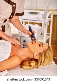 Young woman receiving electric ultrasonic facial massage at beauty salon. Hardware cosmetology.