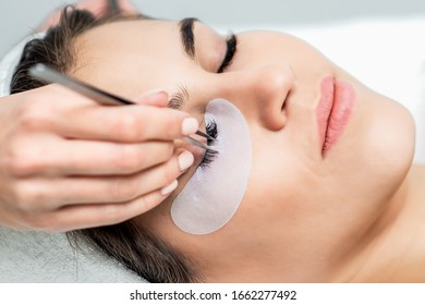 Young woman receiving eyelash extension procedure in beauty salon.
