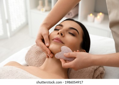 Young woman receiving facial massage with gua sha tool in beauty salon