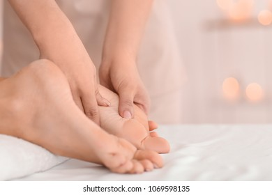 Young woman receiving feet massage in spa salon, closeup