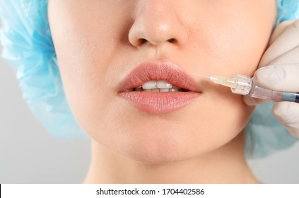 Young woman receiving filler injection on grey background, closeup
