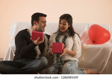 young woman receiving a gift from her boyfriend and surprised