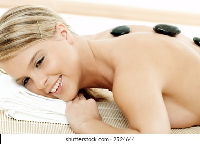 Young woman receiving lastone therapy treatment, eyes open, smiling, close-up