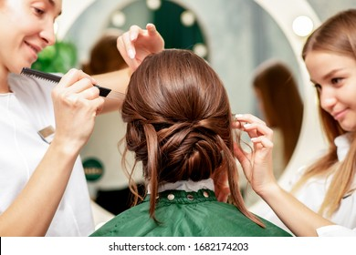 Young woman receiving makeup and hairstyle by professional makeup artist and hairdresser in beauty salon.