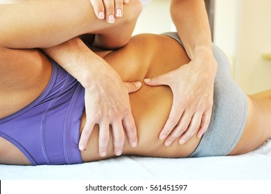 Young woman is receiving osteopathy therapy for back pain relieve
