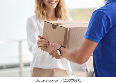 Young woman receiving parcel from courier indoors