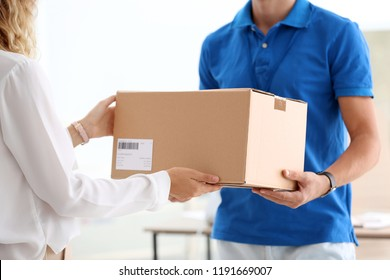 Young woman receiving parcel from courier in office