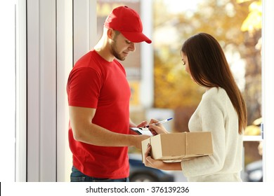 Young woman receiving parcel from delivery man