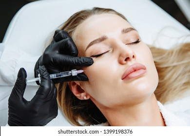 Young woman receiving plastic surgery injection on her face, closeup