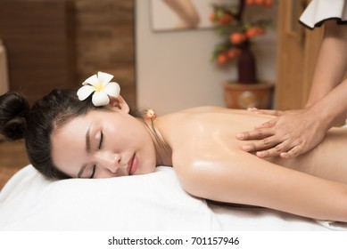 Young woman receiving salt massage in spa salon