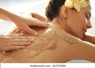 Young woman receiving scrub massage in spa salon
