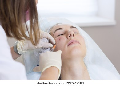 Young woman receiving treatments in beauty clinic. Contouring procedure for face, revitalization, contour plastic with cannula. Beauty injections .