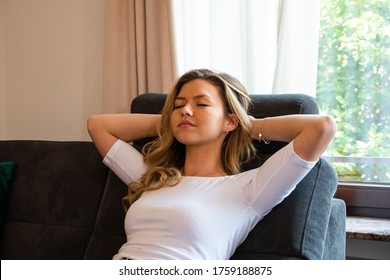 Young woman reclining in sofa recliner. Eyes closed with hands behinds head. Medium shot. Side view.