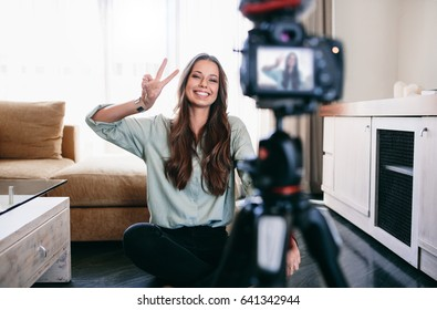 Young woman recording her daily video blog on a tripod mounted camera. Smiling young woman showing victory or peace sign on camera.
