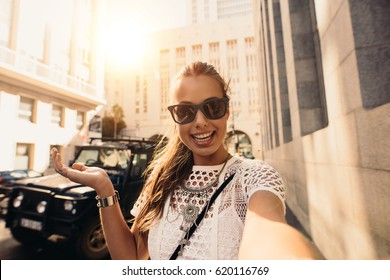 Young woman recording a selfie video in a street. Vlogger recording content for her travel vlog.