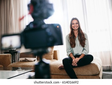 Young woman recording video on camera mounted on a tripod for her vlog. Pretty woman smiling at the camera sitting in her living room.