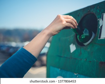 A young woman is recycling a glass bottle at a bottle bank