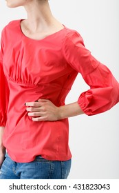 Young woman in a red blouse and jeans on white background