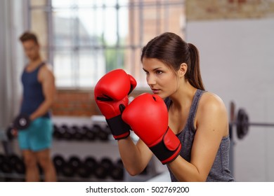 Young woman in red boxing gloves and fighting stance at gym with window and weights in background