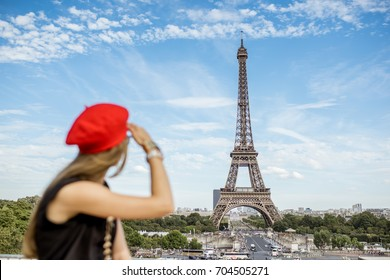 Young woman in red cap and pants enjoying great view on the Eiffel tower in Paris. Woman is out of focus