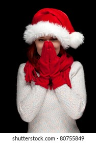 young woman in red Christmas hat and mittens, black background