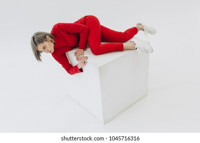 young woman in red clothes lying on white cube