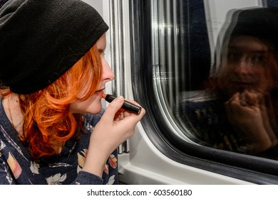Young woman with red curly hair sitting in a train and doing makeup, face reflecting in a window glass, make up in a transport
