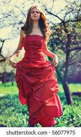 Young woman in red dress in garden. Film style colors.