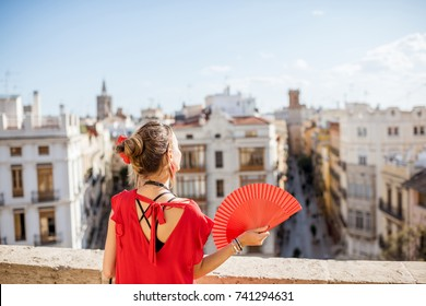 Young woman in red dress with hand fan and photo camera enjoying beautiful cityscape view on Valencia city during the sunny weather in Spain