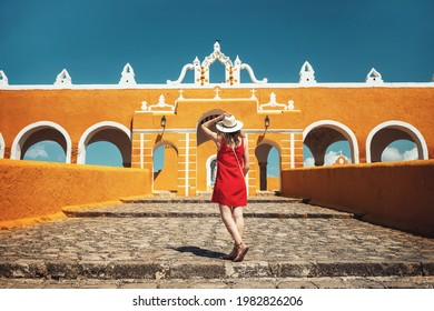 A young woman in a red dress and hat travels through the yellow city of Izamal, Mexico. Lifestyle. Travel to Mexico. Beautiful multicolored cities in Mexico