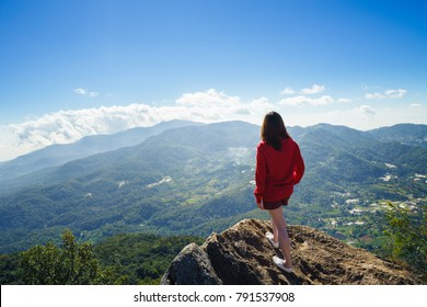 Young woman in red dress looking at blue sky on mountain peak
