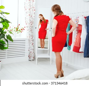 young woman in a red dress looks in the mirror and choose clothes