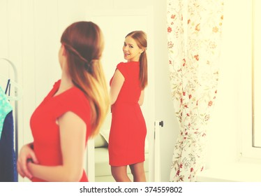 young woman in a red dress looks in the mirror