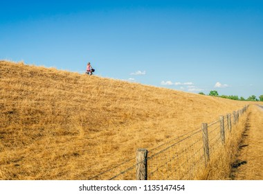 Young woman in a red dress rides on her bike on the top of a Dutch dike. The photo is made on a warm summer evening. The grass on the dike is completely yellowed due to the prolonged drought period.