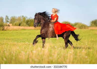 Young woman in red dress riding black horse bareback.
