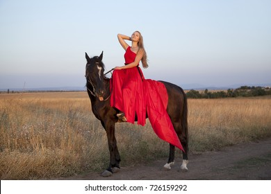 Young woman in a red dress riding a horse. Blonde sitting in the saddle posing in the outdoors. Beautiful girl lifting her head up, looking into the distance